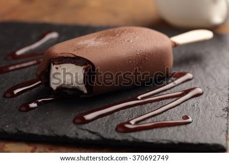 Ice cream bar coated with chocolate on a slate board - stock photo