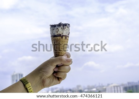 Ice cream cone in hand with blue sky background
