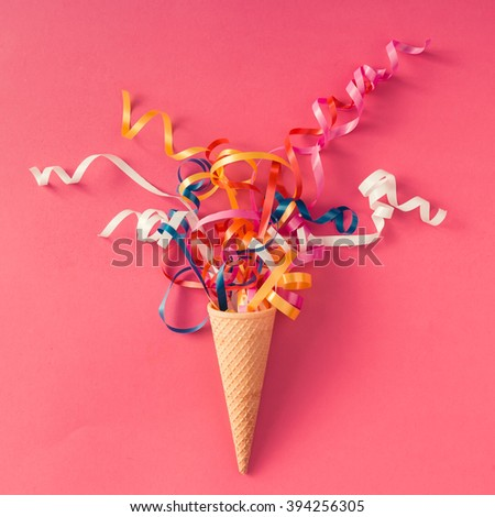 Ice cream cone with colorful party streamers on pink background. Flat lay