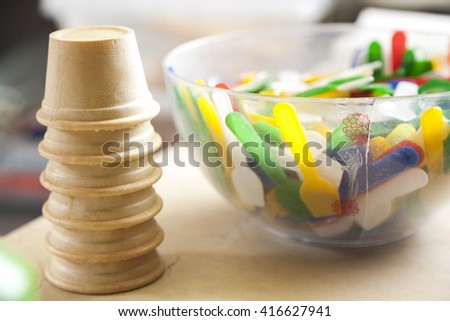 Ice Cream Cups By Multicolored Spoons In Bowl - stock photo