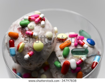 Ice cream garnished with multicolored pills, close-up