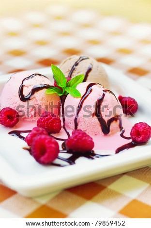 Ice cream in a plate decorated with mint and raspberries (shallow dof) - stock photo