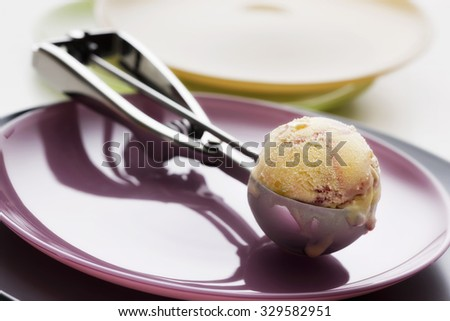 Ice cream in a spoon on a pink dish - stock photo