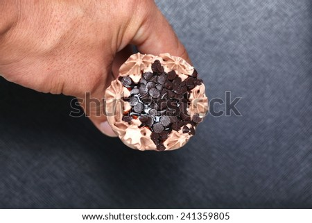 Ice cream in man hand photo caption on black color leather surface background represent the dessert related.