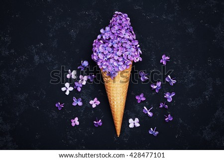 Ice cream of lilac flowers in waffle cone on black background from above, beautiful floral arrangement, vintage color, flat lay styling  - stock photo