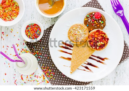 Ice cream pancake with chocolate, jam, peanut butter, colorful sugar. Funny breakfast for kids top view - stock photo