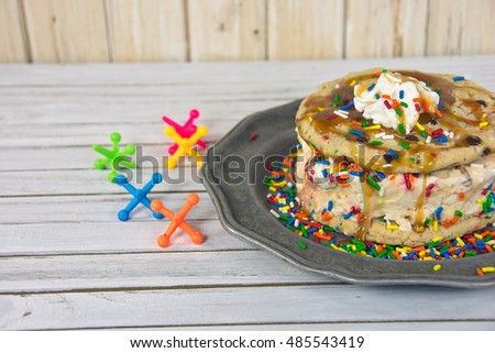ice cream sandwich with toy jacks and sprinkles on pewter plate