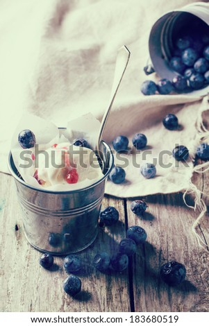 Ice cream, served in little metal pail with blueberries on white wooden table in retro filter effect. - stock photo