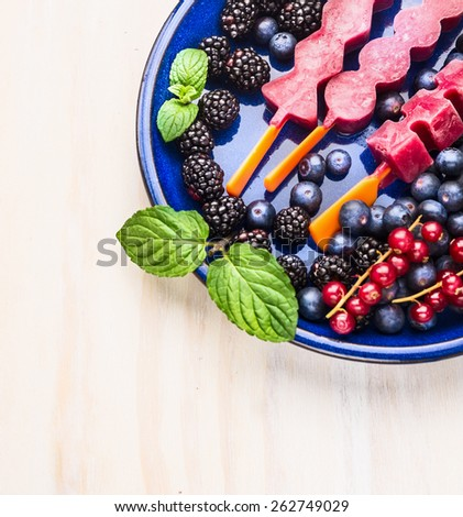 Ice cream sorbet  pops with different summer berries and mint in blue plate on white wooden background - stock photo