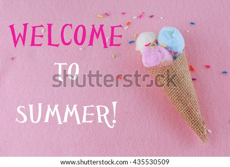 Ice cream waffle cone shape made out of burlap and cotton balls in pink, yellow and blue on pink felt background with multi-colored candy sprinkles. Cone is in the lower right corner. Summer text. - stock photo