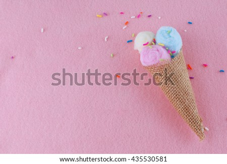 Ice cream waffle cone shape made out of burlap and cotton balls in pink, yellow and blue on pink felt background with multi-colored candy sprinkles. Cone is in the lower right corner. Copy space. - stock photo