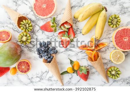 Ice cream waffle cones with fresh ripe fruits - stock photo