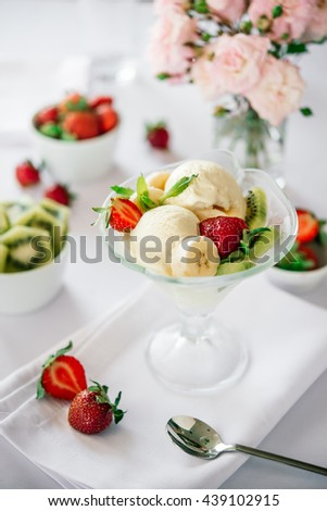 Ice cream with fresh fruits served on white
