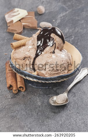 Ice cream with nuts and chocolate topping . Chocolate ice cream scoops with chocolate topping, nuts  and cinnamon on dark granite table. Macro photograph with shallow depth of field.  - stock photo