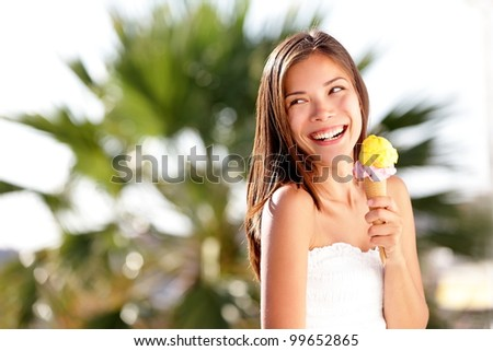 Ice cream woman looking at copy space happy, joyful and cheerful. Cute multiracial Caucasian / Chinese Asian young female model eating ice cream cone on summer beach.