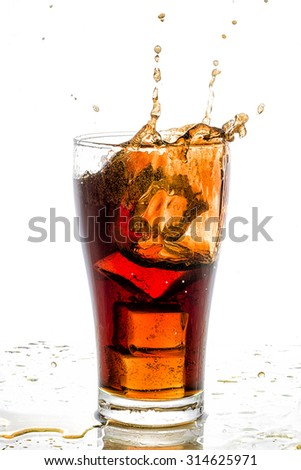 Ice cube droped in cola glass and cola splashing.