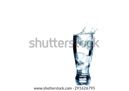 Ice cube dropped into a glass of water making splash with copy space isolated on white background