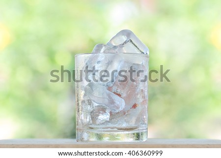Ice cube in glass on blurred natural background - stock photo