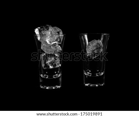 ice cube in two small glass isolated on black background