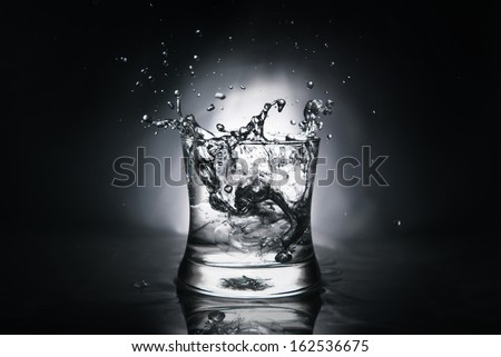 ice cube splashing into a glass full of water - stock photo