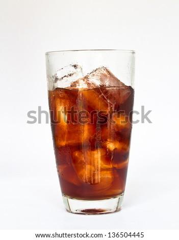 ice cube splashing into glass of coke white background. - stock photo
