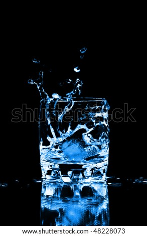 Ice cube splashing into glass of water, isolated on black - stock photo