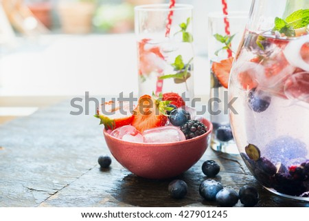 Ice cubes and berries in red bowl on table with glass of water. Summer drink preparation - stock photo