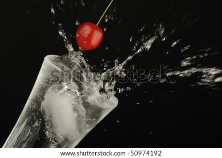 Ice cubes and cherry dropping into a cocktail glass.