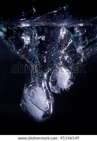 Ice Cubes entering water with splash - stock photo