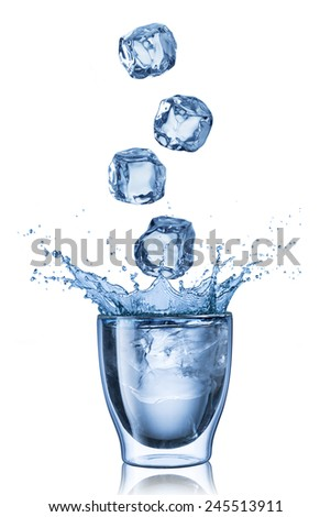 Ice Cubes Falling Into Glass of Water Causing Splash - stock photo