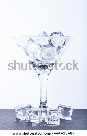 Ice cubes in a martini glass on white background. Toned.