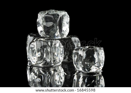 Ice cubes in a pool of water isolated on a black background - stock photo