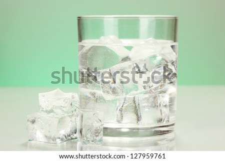 Ice cubes in glass on light green background - stock photo