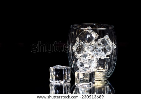 Ice Cubes in glass that is isolated on black background with reflections on the mirrored surface