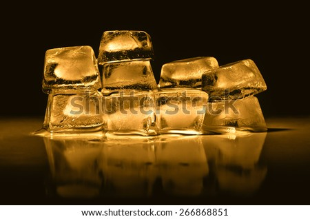 Ice cubes of  gold color on a black background