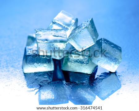 Ice cubes on reflected glass background,blue background - stock photo