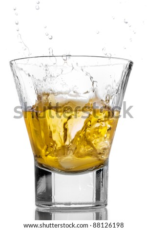 Ice cubes splashing into a glass of whiskey - stock photo