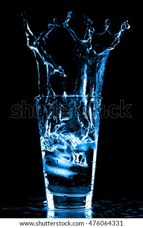 Ice cubes splashing into glass of water, isolated on black background