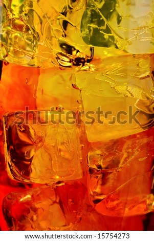 Ice cubes swimming in orange drink. - stock photo