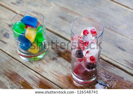 Ice cubes with blueberry and red currant berry and with different colors in summer. Selective focus on glass with berries. - stock photo