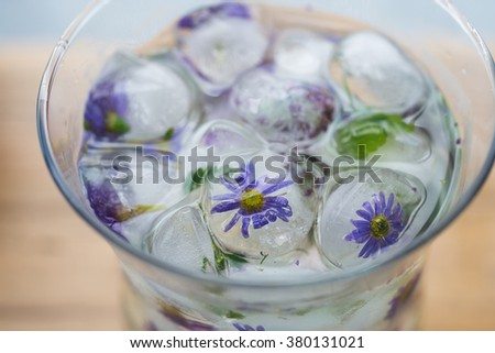 Ice cubes with flowers in water - stock photo