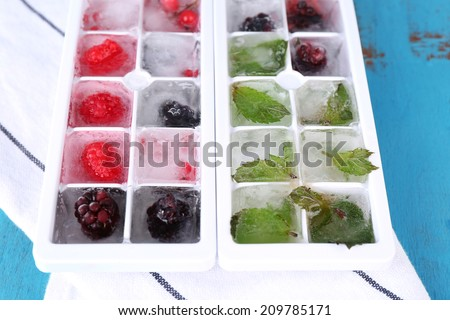 Ice cubes with forest berries, mint leaves in ice cube tray, on color wooden background - stock photo