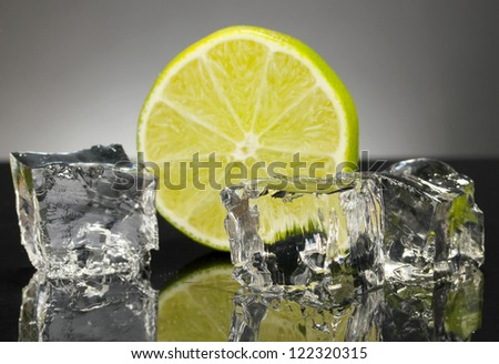Ice cubes with lime on black background - stock photo