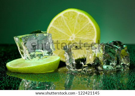 Ice cubes with lime on darck green background - stock photo