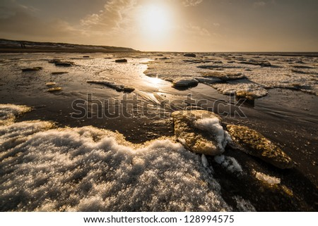 Ice drifted on the shore covered with snow - stock photo