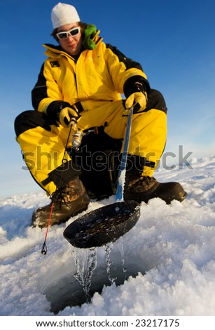 Ice fisherman cleaning ice from the hole with a ladle, focus on the scoop - stock photo