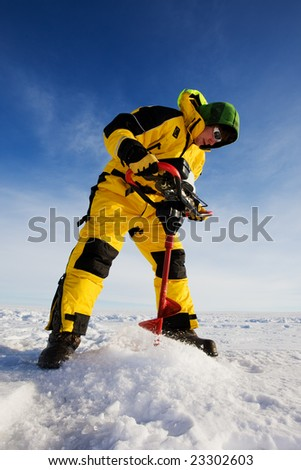 Ice fisherman drilling a hole on a frozen lake with a power auger