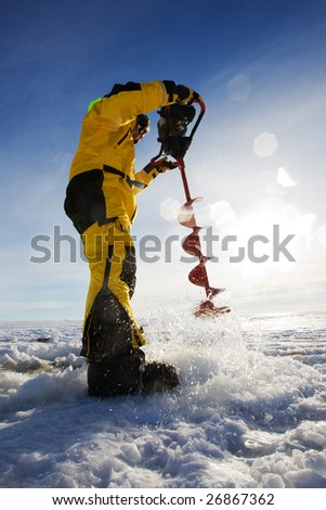 Ice fisherman drilling a hole with a power auger with sun flares