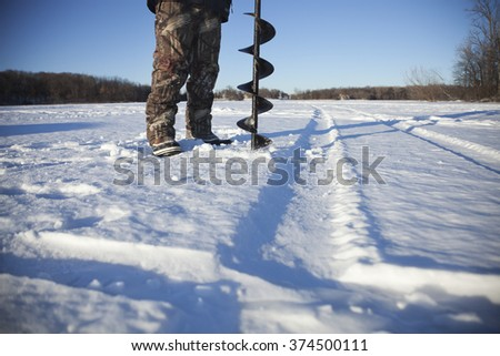 Ice fisherman drills hole in ice on a lake in Minnesota during winter - stock photo