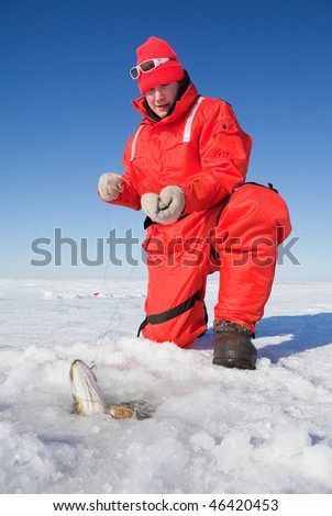 Ice fisherman fighting a northern pike through the ice with a hand line